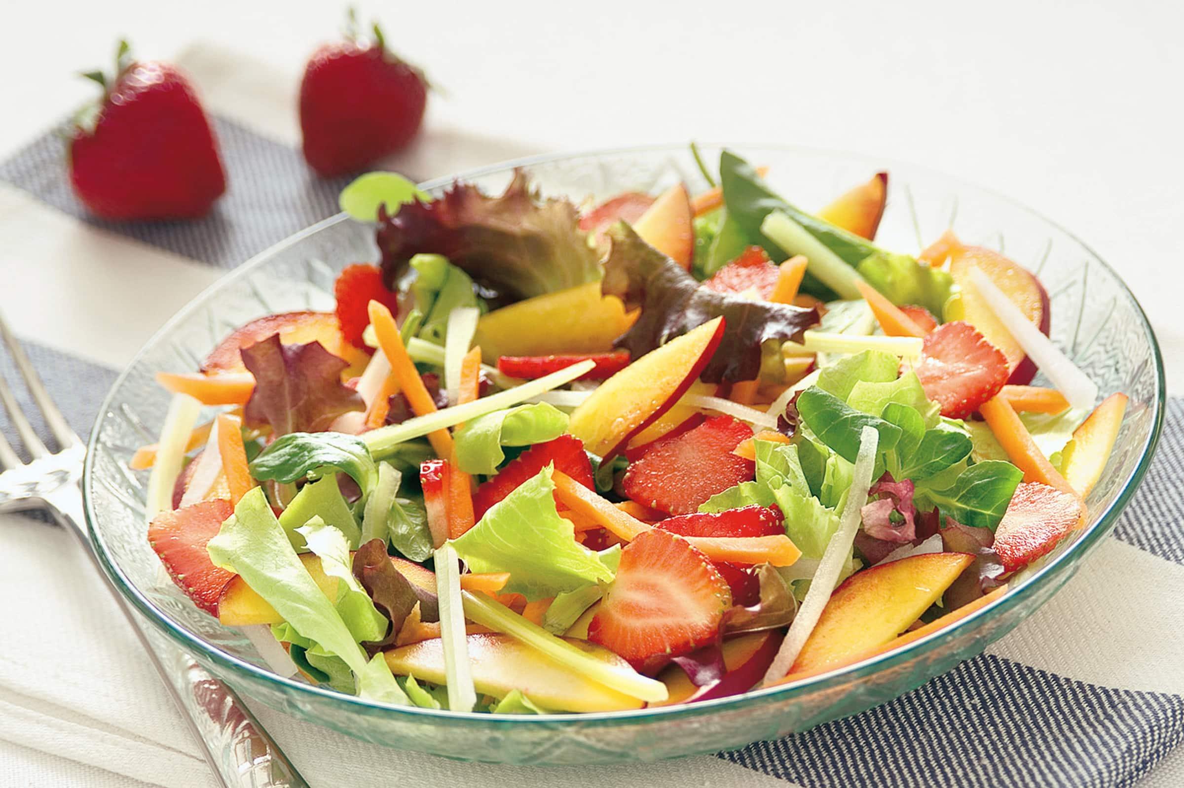 Insalata di misticanza con frutta estiva, semi di lino e provolone piccante